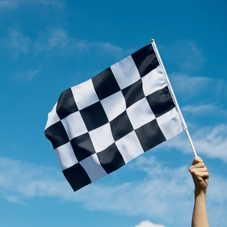 kostkovaný závod vlajkou v ruce.