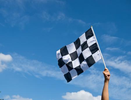 checkered race flag in hand. Reklamní fotografie