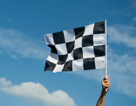 checkered race flag in hand. photo