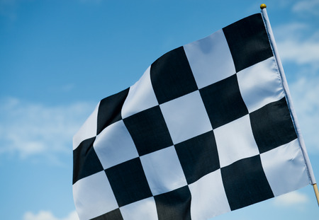 chequered: checkered race flag waving on blue sky.