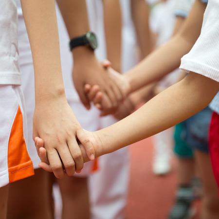 Group of children holding hands together.