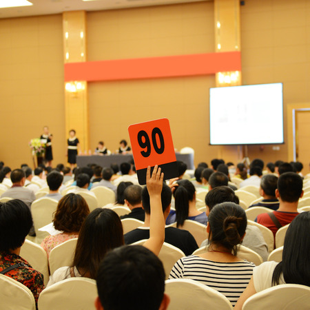 bidding: People holding auction paddle to buy from auction. Stock Photo