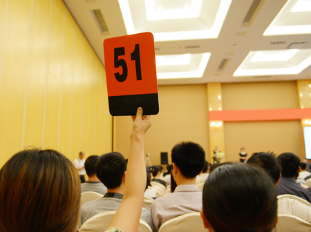 People holding auction paddle to buy from auction. Stock Photo