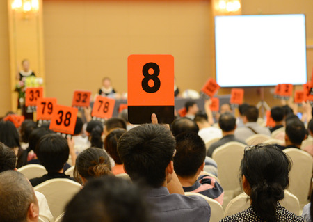 People holding auction paddle to buy from auction. 版權商用圖片 - 33783596