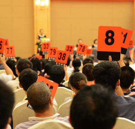 bid: Las personas titulares de paddle subasta para comprar a la subasta. Foto de archivo