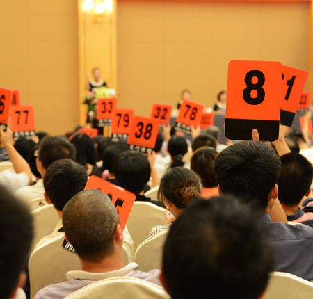 auctioning: People holding auction paddle to buy from auction. Stock Photo