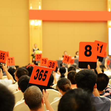 People holding auction paddle to buy from auction. 스톡 콘텐츠