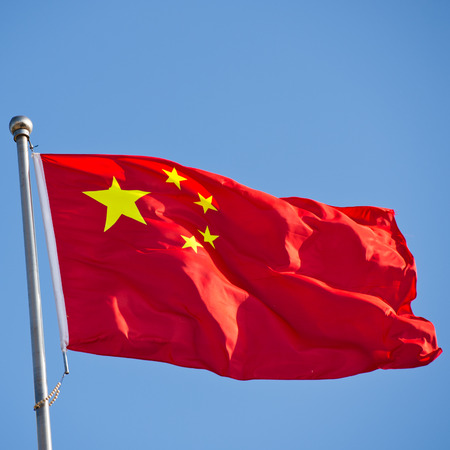 Chinese flag with flag pole waving in the wind over blue sky background. Stock Photo