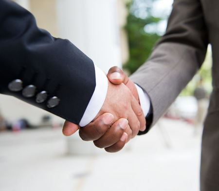 multi race: African businessmans hand shaking white businessmans hand  making a business deal.