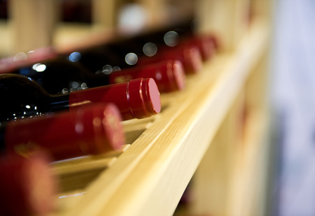 fining: Group of red wine bottles stacked on wooden racks.