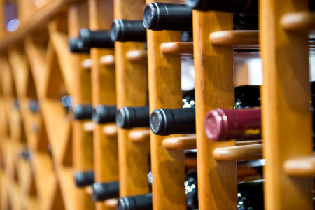 home stores: Group of red wine bottles stacked on wooden racks.
