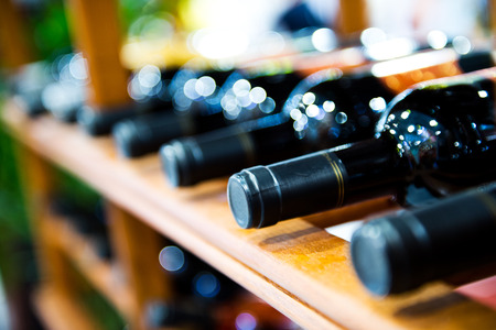 Group of red wine bottles stacked on wooden racks.