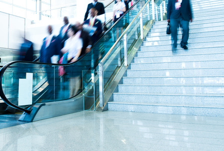 Group of businesspeople moving down on escalator in office. blurred motion.