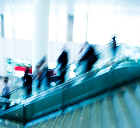 corporate travel: Group of businesspeople moving down on escalator in office. blurred motion.