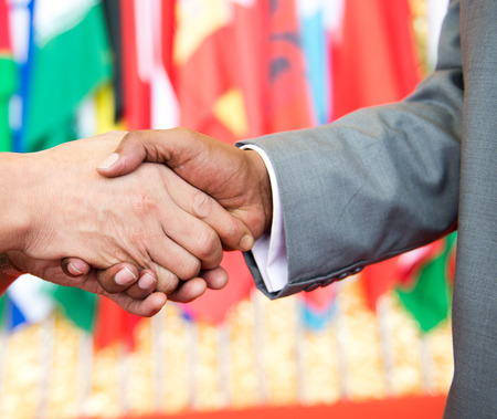 international business agreement: African businessmans hand shaking white businessmans hand  making a business deal.