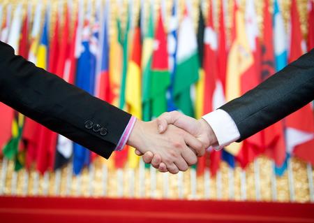 multi national: Businessmen shaking hands in front of the multi - national flag.    international business