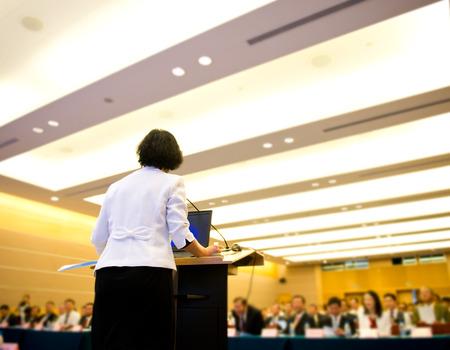 ビジネスの女性は、会議ホールで大勢の聴衆の前でスピーチを作っています。