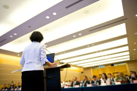 ビジネスの女性会議ホールで大きな観客の前でスピーチを作っています。 写真素材