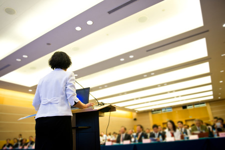 speaking: Business woman is making a speech in front of a big audience at a conference hall.