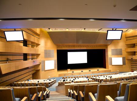 interior de una sala de conferencias con pantalla.