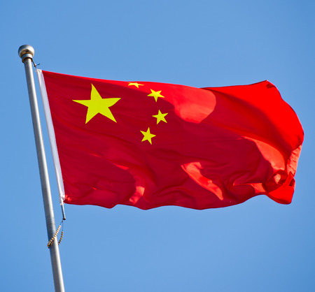 peoples: Chinese flag with flag pole waving in the wind over blue sky background. Stock Photo