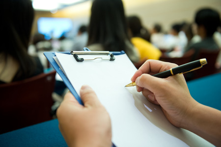 file clerks: people writing on the document in a business seminar.