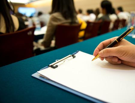 mensen schrijven op het document in een business seminar.