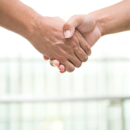 hands shaking: Two men shaking hands in a modern office building.