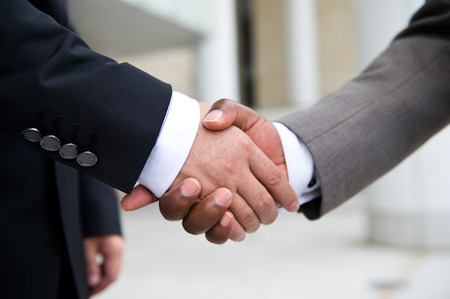 deal making: African businessmans hand shaking white businessmans hand  making a business deal.