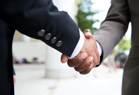 アフリカの実業家のビジネス取引を行って振動白ビジネスマンの手を手します。 写真素材