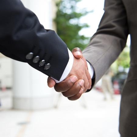 amarillo y negro: La mano de negocios africano estrechando la mano de hombre de negocios blanco que hace un negocio. Foto de archivo
