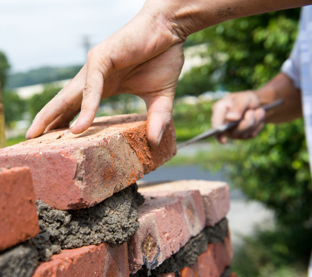 home builder: builder laying bricks in site.