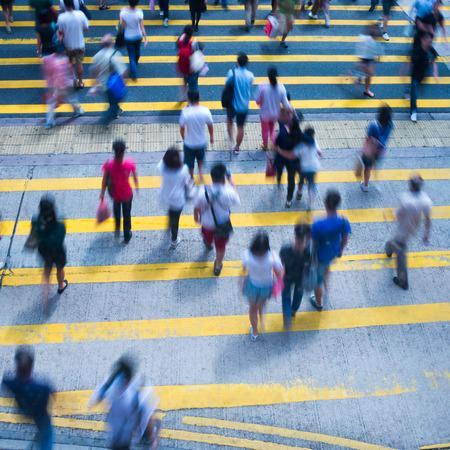 población: Gente de la ciudad ocupada de cebra que cruzan la calle en Hong Kong, China.