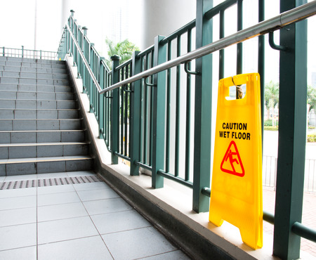 Wet floor caution sign near the stairs. Foto de archivo