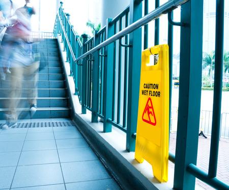 Wet floor caution sign near the stairs. Foto de archivo