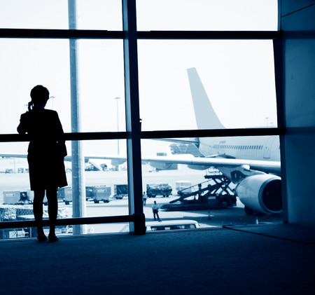 airport window: woman standing near the airport window, waiting for flight departure.