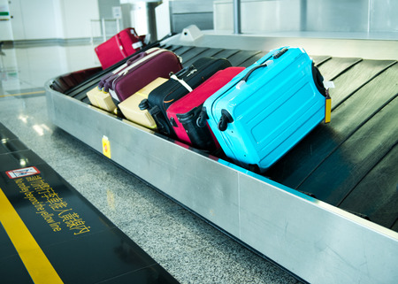 arriving: suitcases on conveyor belt of airport. Stock Photo