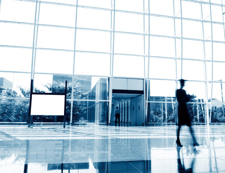 unrecognizable people: Modern interior hall with unrecognizable people walking and blank billboard.