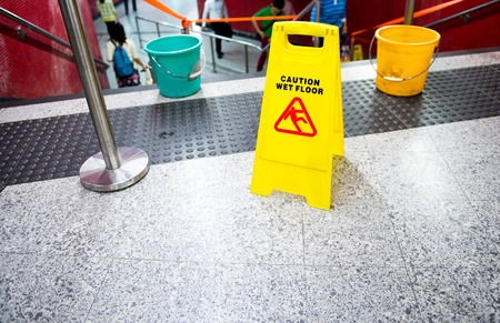 prevented: Wet floor caution sign near the stairs. Stock Photo
