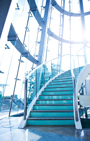 balustrade: Interior of a modern glass building with stairs.
