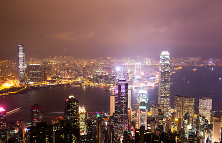 ifc: Hong Kong cityscape at night with victoria harbour and large group of tall buildings.