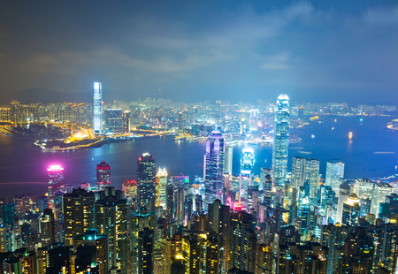 icc: Hong Kong cityscape at night with victoria harbour and large group of tall buildings.