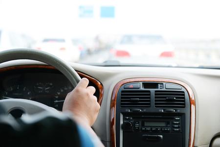 Human hand on steering wheel inside of a car.