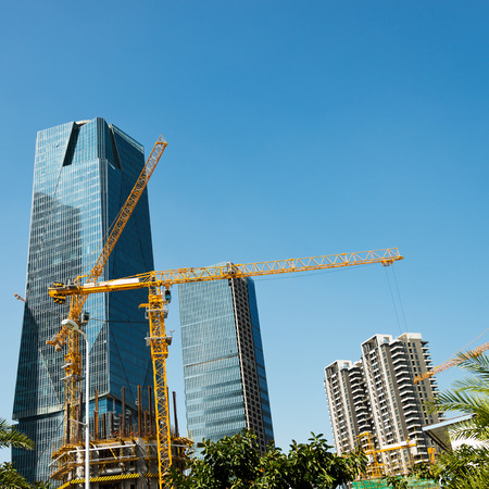 Construction site with cranes on blue sky background. photo