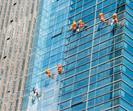 steeplejack: Workers of steeplejack washing windows of the modern building. Stock Photo