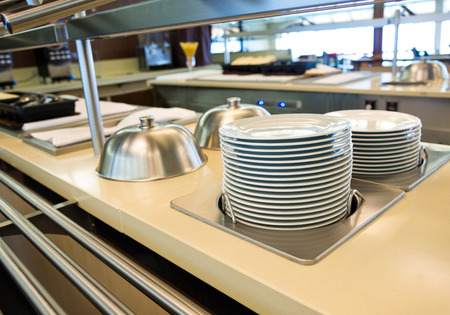 dish washing: Group of white plates stacked together in a hotel.