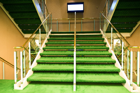 Green carpet on a stairway in a luxury cruise.