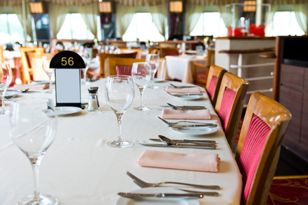 dinner cruise: fork and knife on a napkin with plate. Stock Photo