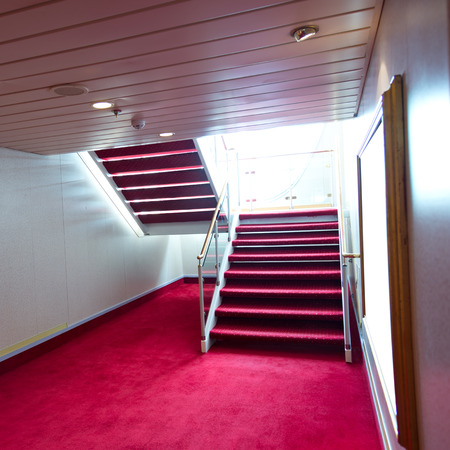 Red carpet on a stairway in a luxury cruise. photo