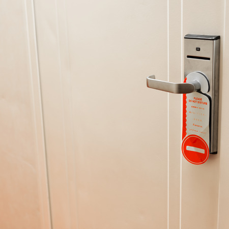 hotel door: Do not disturb sign hang on hotel door knob.